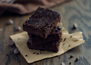 Stack of 3 paleo brownies on a piece of brown parchment paper with brownie crumbs and chocolate chips around and a brown towel behind all on a wooden surface