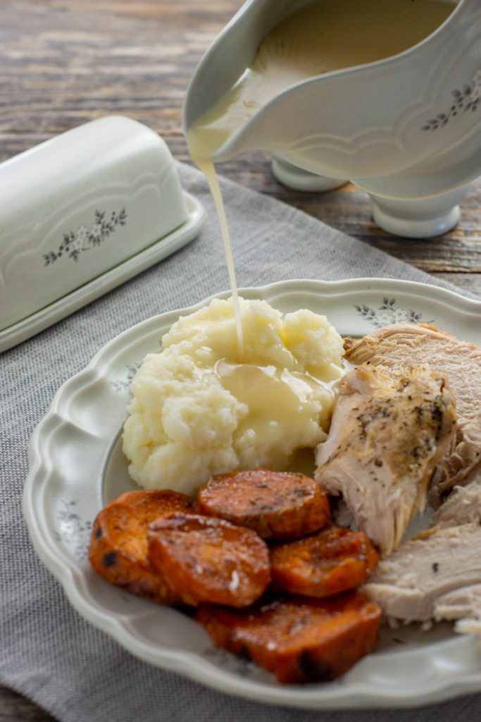 Turkey gravy being poured onto a plate with mashed potatoes, turkey, and candied yams with a butter dish behind on top of a grey placemat on a wooden surface (vertical)