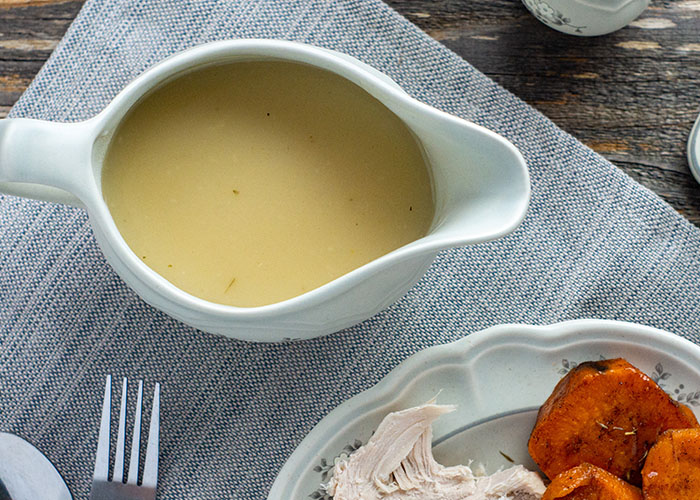 Overhead view of turkey gravy in a white gravy boat next to a plate with turkey and yams on a grey placemat on a wooden surface