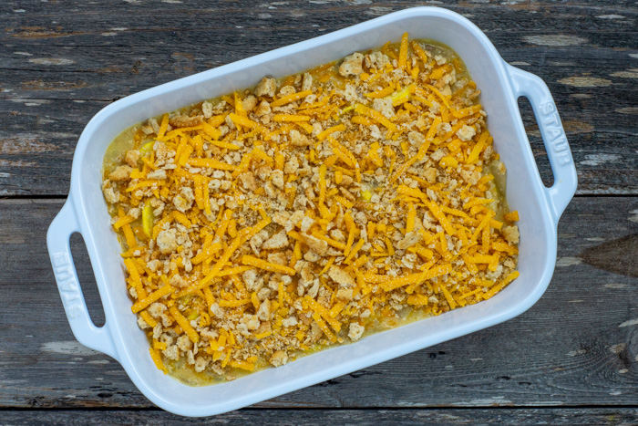 Yellow squash mixture covered with remaining cracker and cheese mixture in a white rectangular casserole dish on a wooden surface