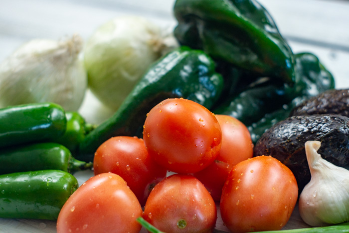 Close-up of recently washed tomatoes, peppers, avocados, garlic, and onions