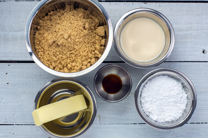 Ingredients for brown sugar fudge in stainless steel bowls on a white wooden surface: brown sugar, evaporated milk, powdered sugar, vanilla extract, and butter