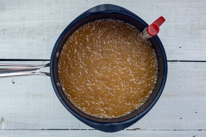 Butter and brown sugar boiling in a saucepan with a candy thermometer in it on a white wooden surface