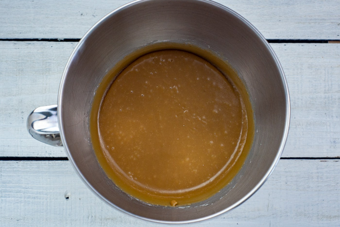 Fudge mixture in a stainless steel bowl on a white wooden surface