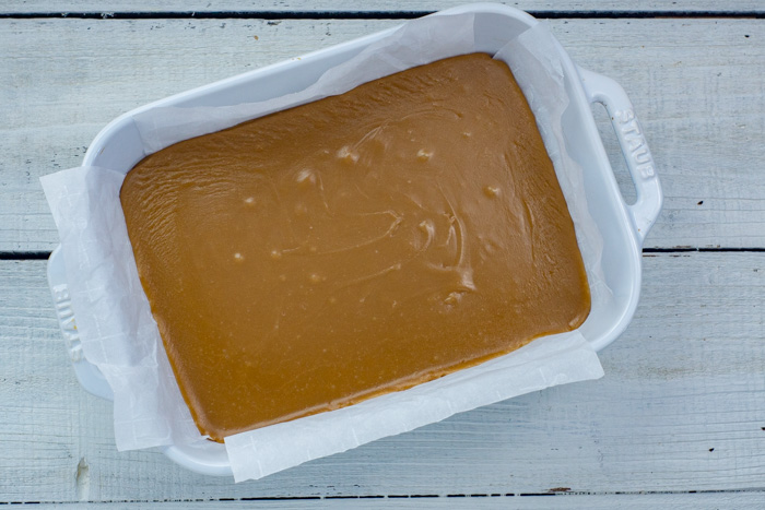 Brown sugar fudge in a parchment-paper lined white casserole dish on a white wooden surface
