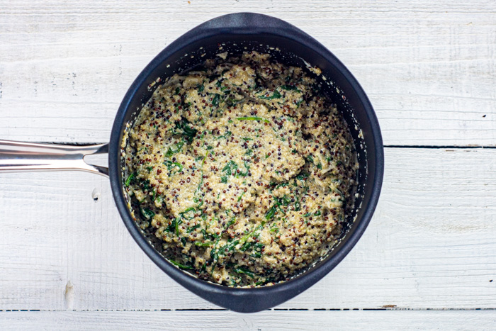 Cooked quinoa with spinach and melted cheese in a saucepan on a white wooden surface