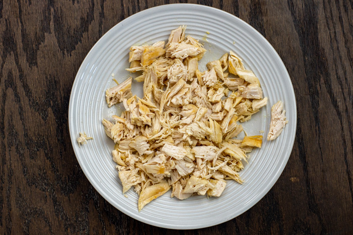 Shredded cooked chicken on a round white plate on a wooden surface