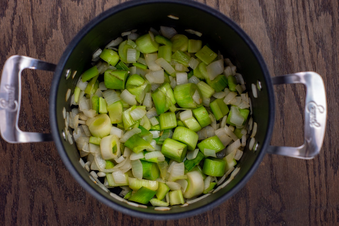 Diced leeks and onions in a large stockpot on a wooden surface