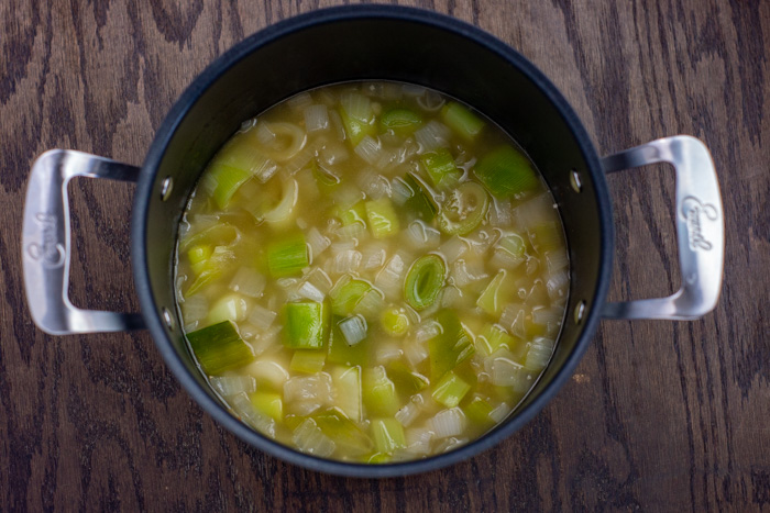 Diced vegetables in broth in a large stockpot on a wooden surface