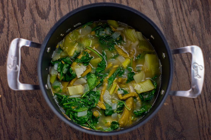 Diced vegetables in broth with wilted spinach and asparagus in a stockpot on a wooden surface
