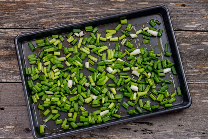Chopped green onion drizzled with oil on a rimmed baking sheet on a wooden surface