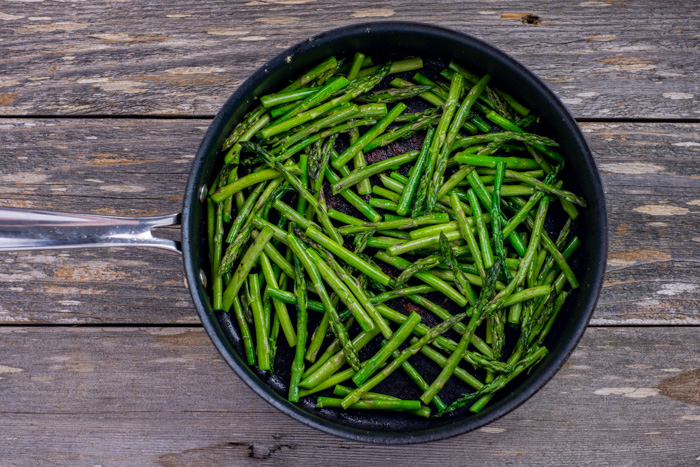 Asparagus in a skillet on a wooden surface
