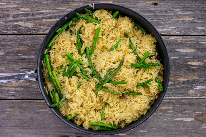 Cooked orzo with asparagus in a skillet on a wooden surface