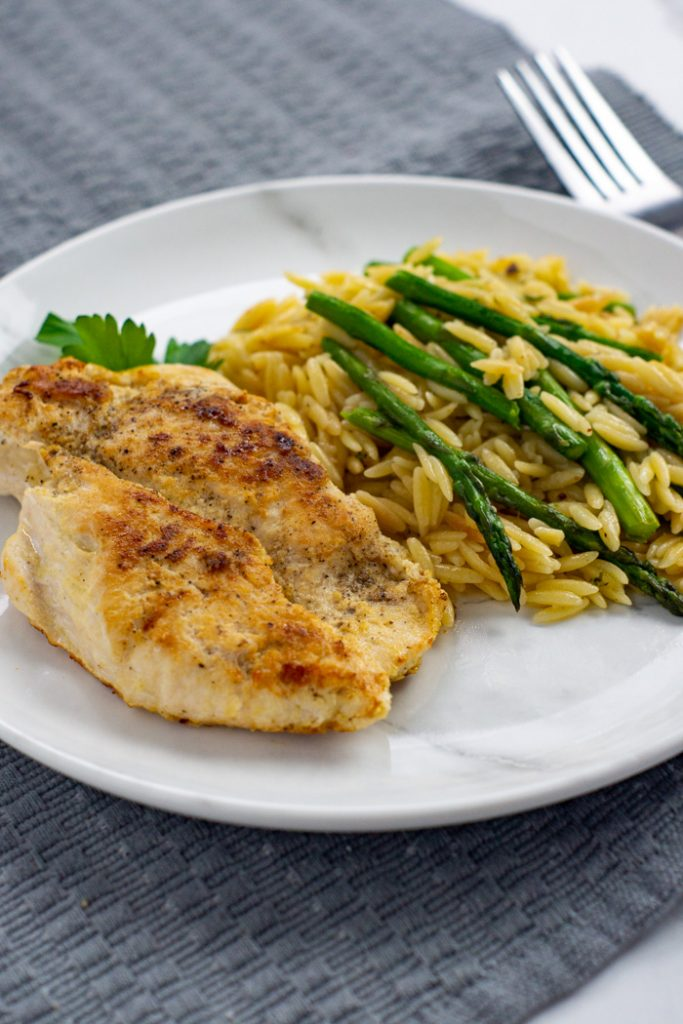 Honey Mustard Chicken with Orzo and asparagus on a round white and grey marble plate on top of a grey placemat with a stainless steel fork next to the plate all on a white surface