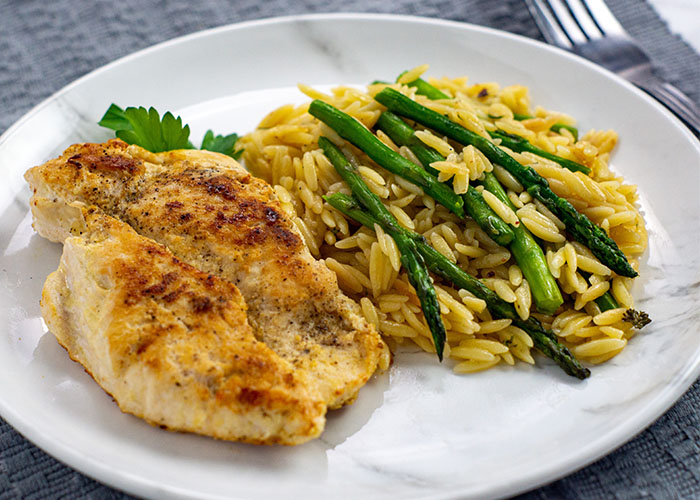 Honey Mustard Chicken with Orzo and asparagus on a white and grey marbled plate on top of a grey placemat