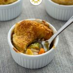 3 mini chicken pot pies in round white ramekins with a stainless steel spoon on a grey cloth surface (with title overlay)