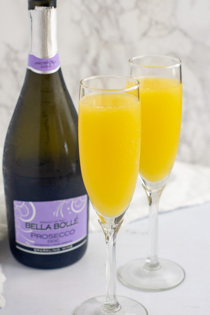 Two prosecco mimosa drinks in champagne flutes in front of a bottle of prosecco with a white towel behind all on a white surface (vertical)