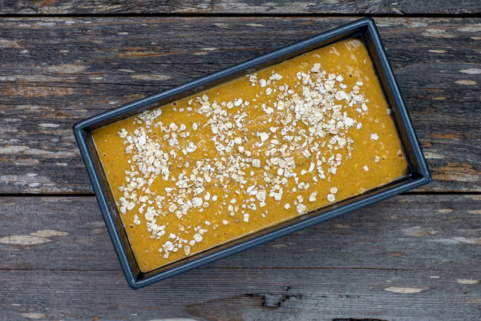 Pumpkin maple bread batter sprinkled with oats in a metal loaf pan on a wooden surface