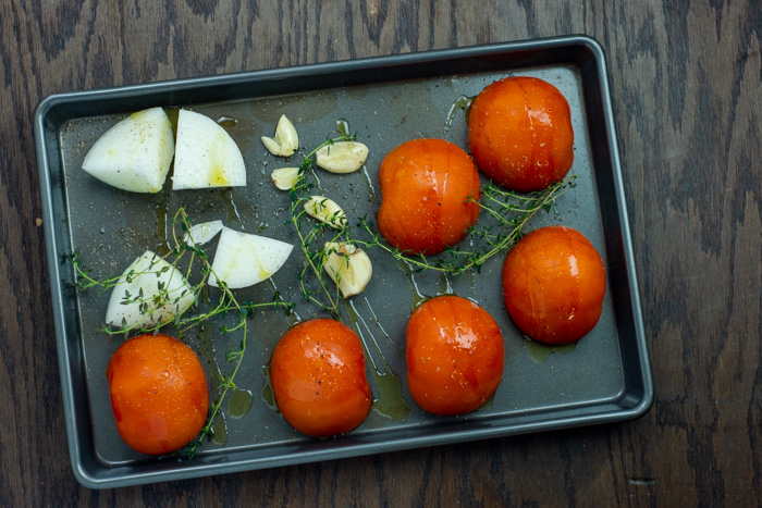 Tomatoes, onion, and garlic drizzled with oil and seasoned with sprigs of thyme on a rimmed baking sheet on a wooden surface