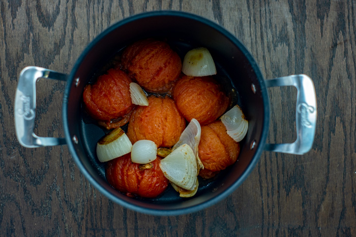 Peeled roasted tomatoes and onions in a large stockpot on a wooden surface