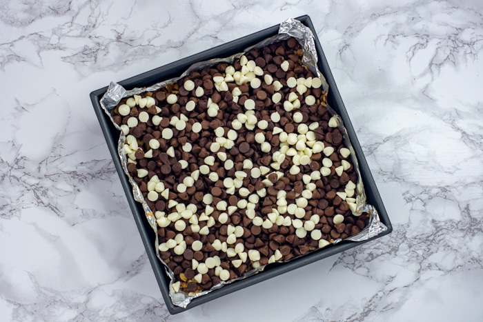 Chocolate chips on crust in a foil-lined metal baking dish on a white and grey marble surface