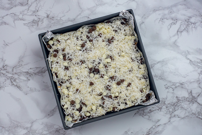 Chocolate chips sprinkled with coconut flakes in a foil-lined metal baking dish on a white and grey marble surface