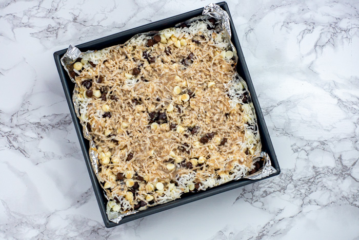 Topping mixture poured over chocolate and coconut in a foil-lined metal baking dish on a white and grey marble surface