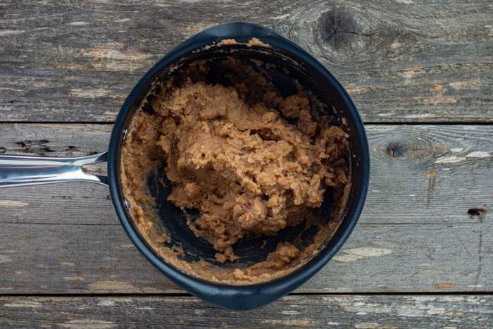 Refried beans heated in a medium saucepan on a wooden surface