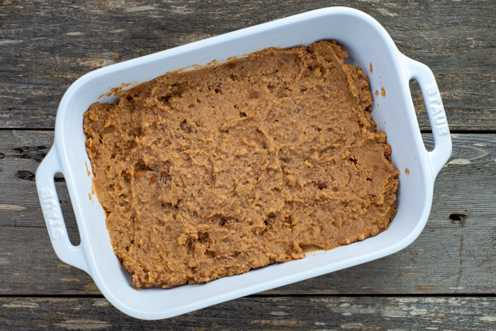 Refried beans in a rectangular white casserole dish on a wooden surface