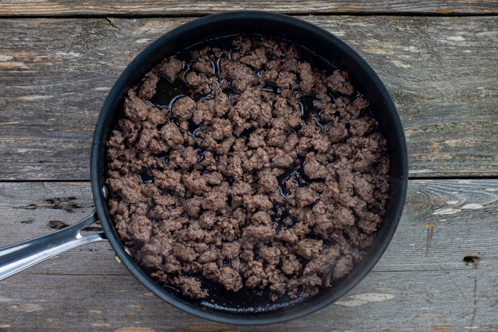Ground beef browning in a skillet on a wooden surface