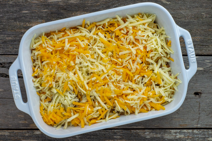 Cheese layer on top of the 5 layer bean dip in a rectangular white casserole dish on a wooden surface