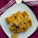 Pile of brown sugar fudge on a square white plate on a red and white towel (with title overlay)