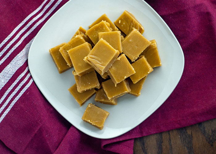 Pile of brown sugar fudge on a square white plate on a red and white towel