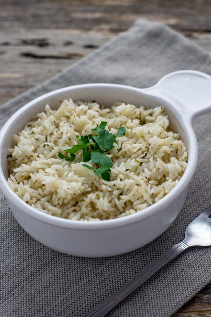 Simple Herbed Rice Side garnished with parsley leaves in a round white bowl next to a stainless steel fork on a grey placemat on a wooden surface (vertical)
