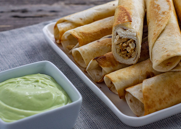 Chicken flautas piled on a square white platter next to a small square white dish with buttermilk avocado sauce on a grey placemat all on a wooden surface (with title overlay)
