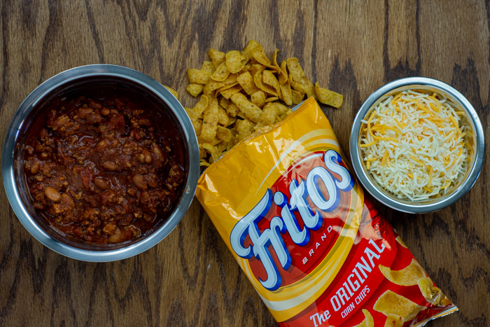 Prepared chili in a stainless steel bowl next to a bag of Fritos next to a stainless steel bowl of shredded cheese all on a wooden surface