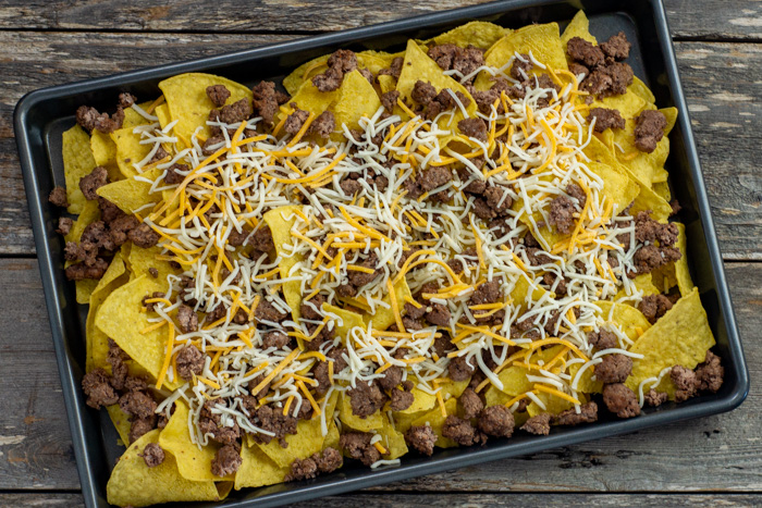Tortilla chips covered with ground beef and shredded cheese on a metal baking sheet on a wooden surface