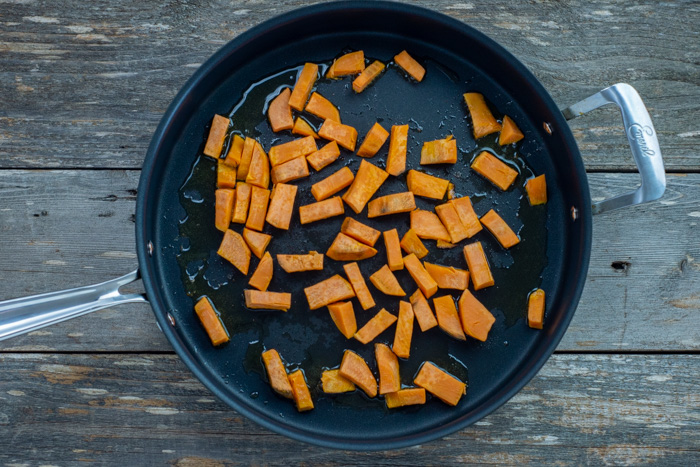 Diced sweet potato in a skillet over a wooden surface