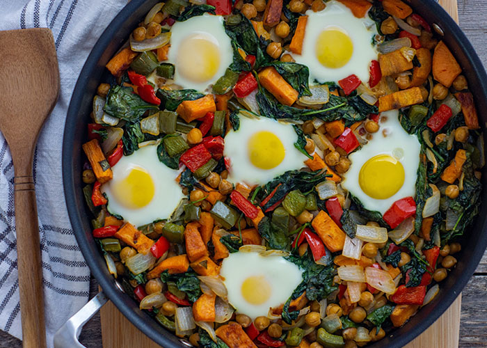 Healthy breakfast hash of sweet potatoes, chickpeas, bell peppers, onion, spinach, and eggs in a skillet on a bamboo cutting board with a white and grey towel behind all on a wooden surface