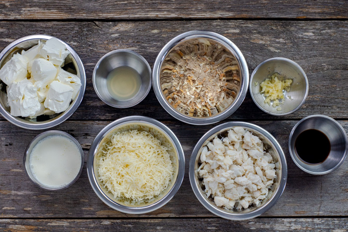 Ingredients for hot crab dip in stainless steel bowls on a wooden surface