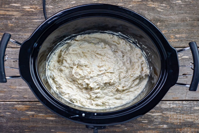 Hot crab dip whisked in a slow cooker on a wooden surface