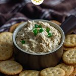 Hot crab dip topped with sliced green onion in a round brown bowl surrounded by Ritz crackers on a brown plate with a brown and white towel behind (with title overlay)