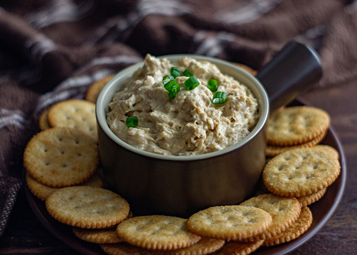 Hot crab dip topped with sliced green onion in a round brown bowl surrounded by Ritz crackers on a brown plate with a brown and white towel behind