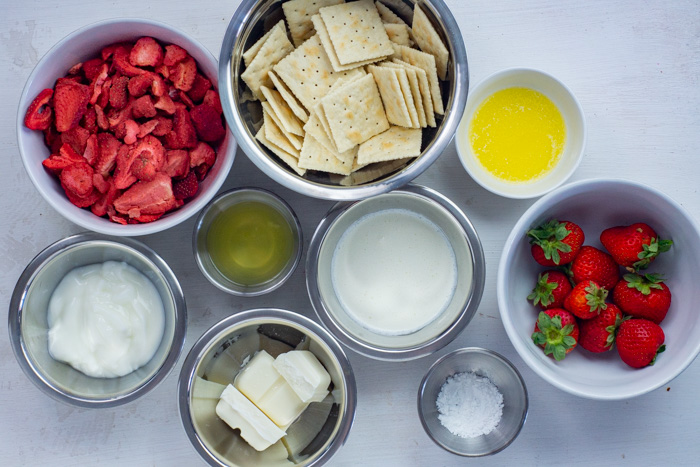 Ingredients for white chocolate strawberry dessert bars in bowls on a white surface