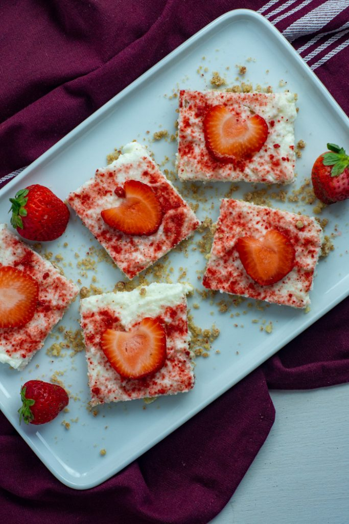 White chocolate strawberry dessert bars with whole strawberries and dried strawberry powder on a long white dish on top of a red and white placemat on a white surface (vertical)