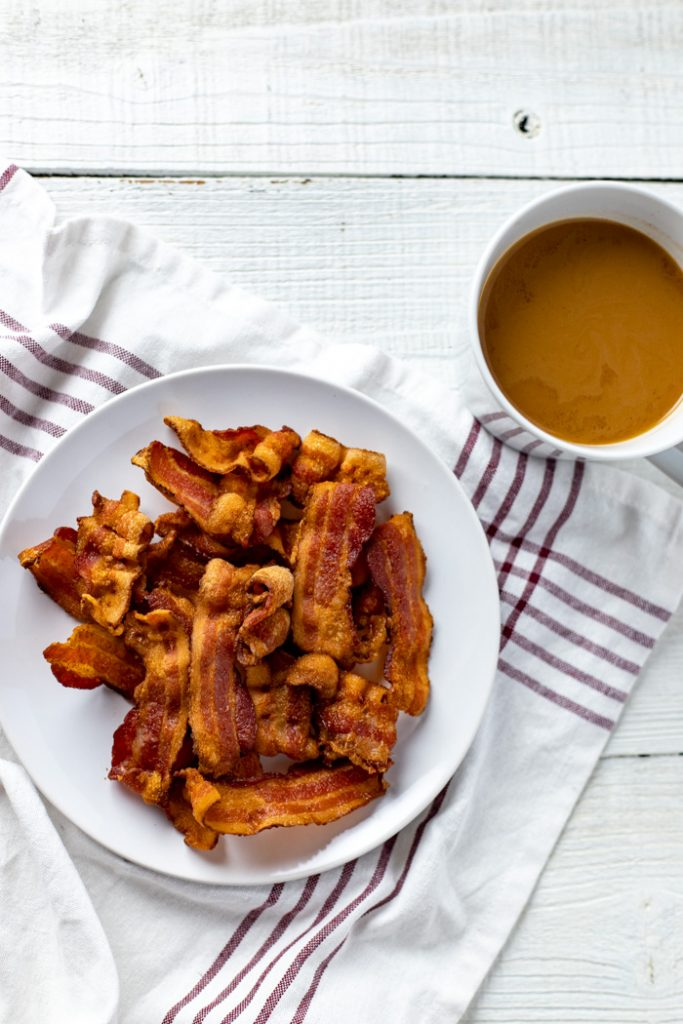 Pile of crispy cooked bacon on a round white plate on a white and red towel next to a white mug of coffee all on a white wooden surface (vertical)
