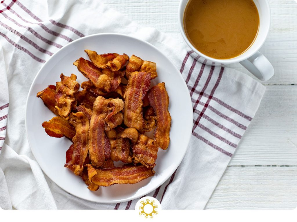 Pile of crispy cooked bacon on a round white plate on a white and red towel next to a white mug of coffee all on a white wooden surface (with logo overlay)