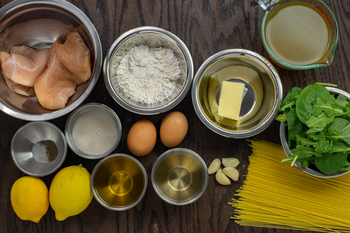 Ingredients for chicken francese in stainless steel bowls on a wooden surface
