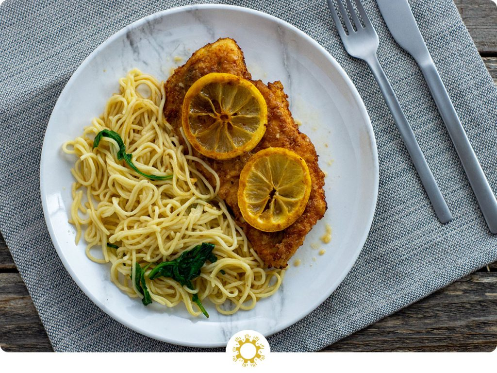 Chicken francese topped with sliced lemons next to angel hair pasta on a round white plate with stainless steel silverware in the back on a grey placemat all on a wooden surface (with logo overlay)