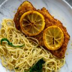 Chicken francese topped with sliced lemons next to angel hair pasta on a round white plate with stainless steel silverware in the back on a grey placemat all on a wooden surface (with title overlay)